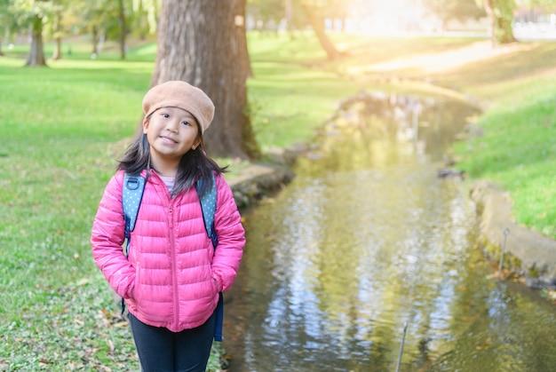 Portret cute girl nosić różowy dół kurtki w parku,