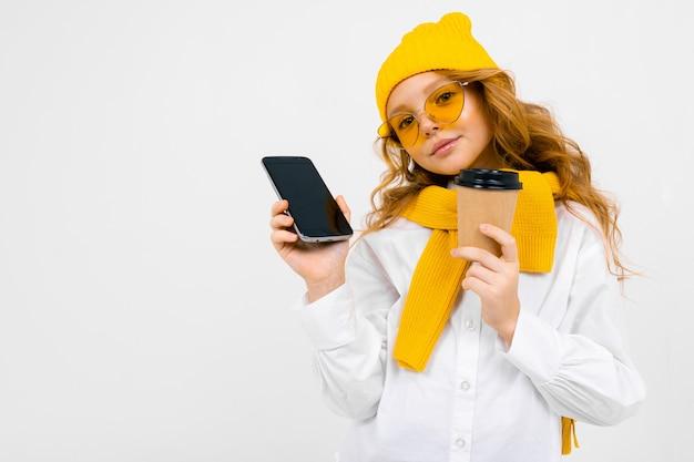 Portret cute kaukaska dziewczyna nastolatka w czapka zimowa i szalik z telefonem z tektury w dłoni i kubek papierowy na białym