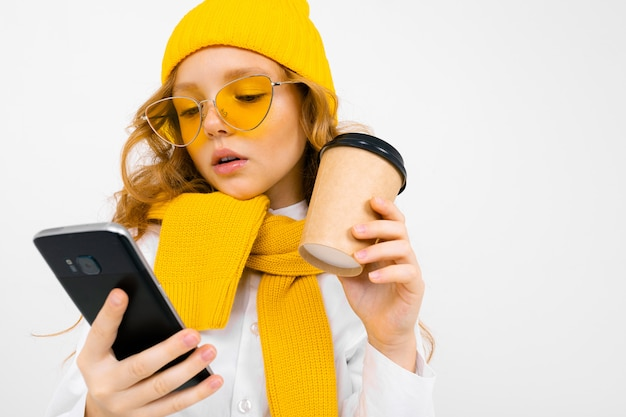 Portret cute kaukaska dziewczyna w czapka zimowa i szalik z telefonem w ręku i kubek papierowy na białym tle z miejsca na kopię
