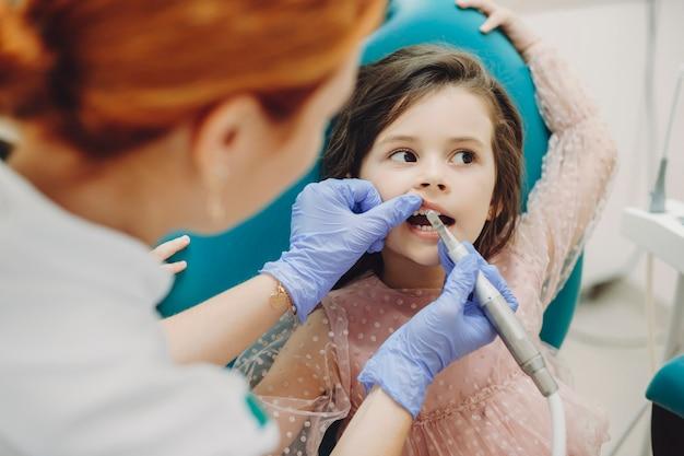 Portret cute little girl robi operacji zębów, podczas gdy ona trzyma z rękami z siedzenia stomatologii i odwracając.