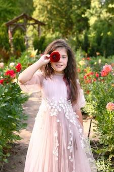 Portret cute little girl z długimi włosami na sobie długą lekką sukienkę w ogrodzie. dziewczyna zakryła oczy kwiatkiem