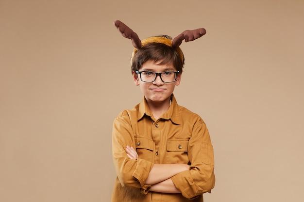 Portret cute nastoletniego chłopca na sobie poroże jelenia i okulary, stojąc z rękami skrzyżowanymi na beżowym tle w studio, kopia przestrzeń
