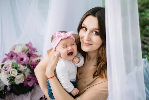 Portret cute noworodka płacz przed matką, podczas gdy ona trzyma ją i próbuje ją pocieszyć