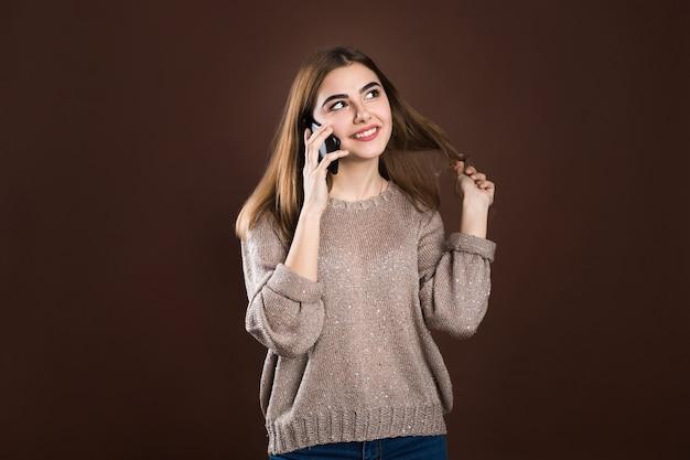 Portret cute szczęśliwa dziewczyna w swetrze rozmawia przez telefon komórkowy i śmiejąc się na białym tle na tle swetra