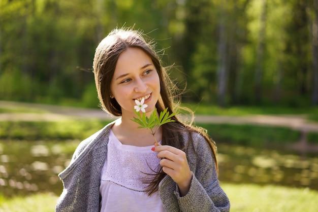 Portret cute szczęśliwa kobieta na tle jeziora, trzymając kwiat do twarzy w słoneczny wiosenny dzień