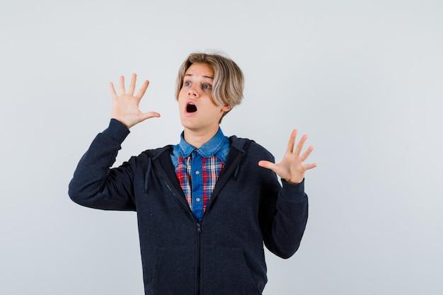 Portret cute teen chłopiec pokazujący gest kapitulacji w koszuli, bluzie z kapturem i patrząc przerażony widok z przodu