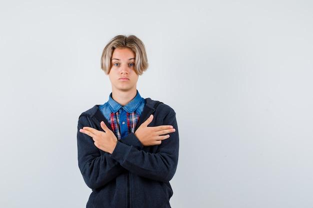 Portret cute teen chłopiec pokazujący gest pistoletu w koszuli, bluzie z kapturem i patrząc zamyślony widok z przodu
