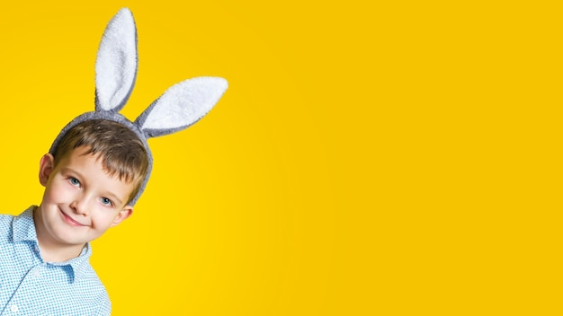 Portret cute uśmiechnięty chłopiec sobie uszy easter bunny na żółto