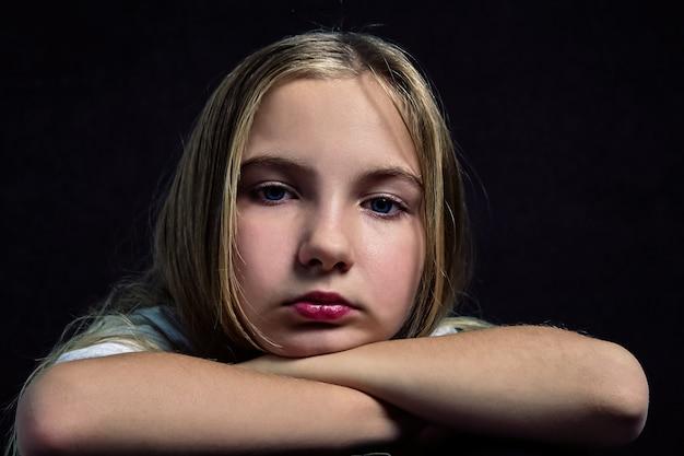 Portret cute zamyślony nastolatka z długimi włosami.