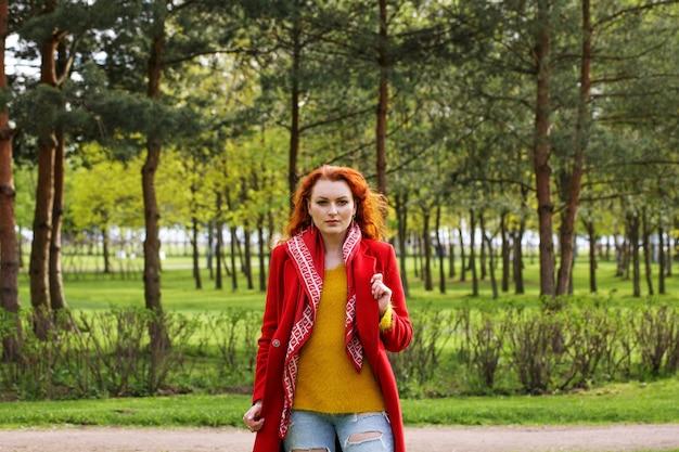 Portret cuteredhaired kobieta w czerwonym płaszczu na zielonym wiosennym parku
