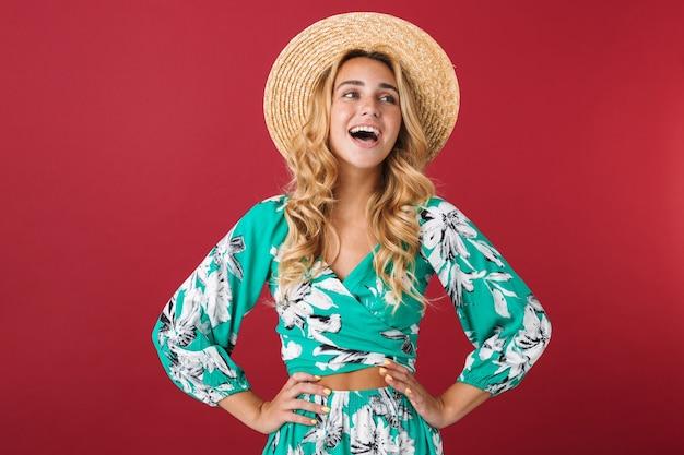 Portret cutie śmiejąca się szczęśliwa młoda piękna blondynka śliczna kobieta w sukni pozuje na białym tle nad czerwoną ścianą patrząc na bok