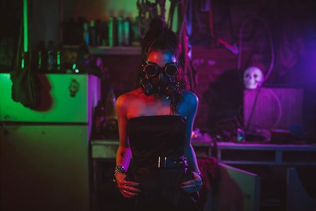 Portret cyberpunkowej dziewczyny w masce gazowej i okularach w stylu postapokalipsy. styl steampunkowy z neonowym światłem
