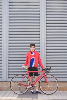 Portret cyklisty atlety pozycja przeciw szarej ścianie z czerwonym rowerem drogowym