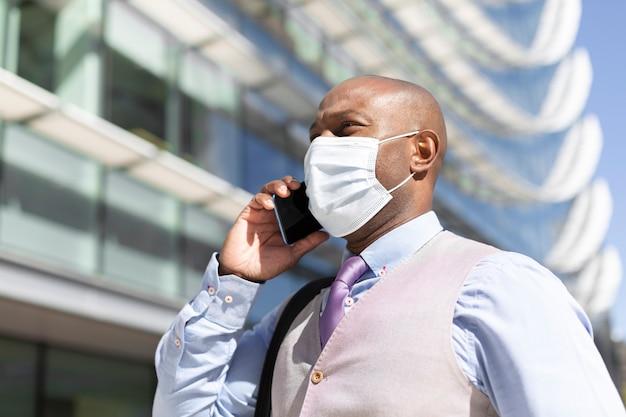 Portret czarnego biznesmena rozmawia przez telefon.