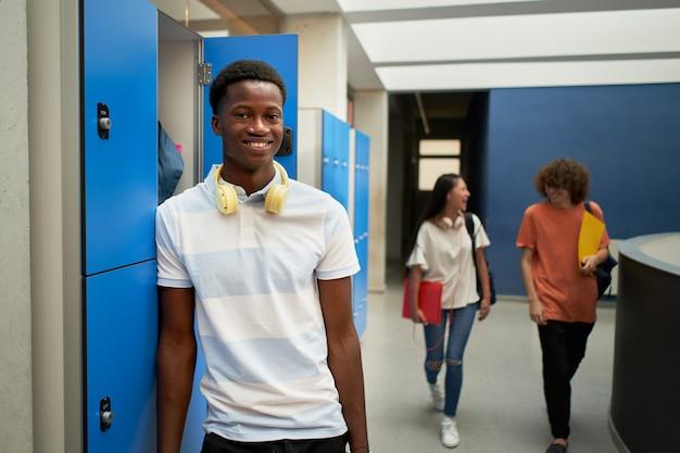 Portret czarnego chłopca studenta patrzącego na uśmiechniętą kamerę w szkole