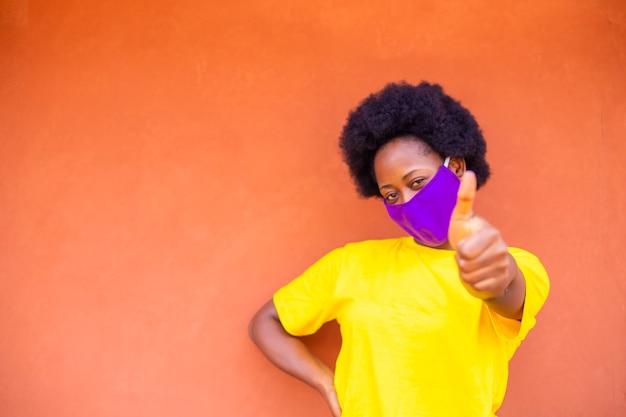 Portret czarnej afrykańskiej kobiety tysiąclecia noszącej maskę na twarzy, biorąc pod uwagę znak