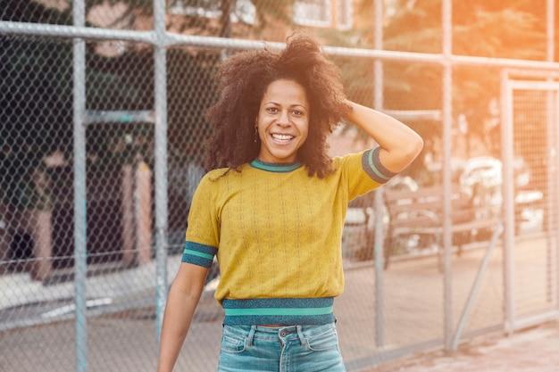 Portret czarnej kobiety w średnim wieku z włosami afro na ulicy z metalowym płotem. ona się uśmiecha.
