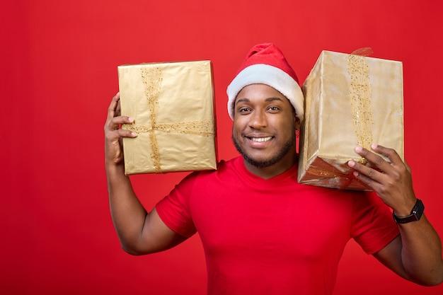 Portret czarnoskórego faceta z otwartymi ustami w kapeluszu świętego mikołaja trzymającego na ramionach prezenty świąteczne