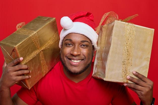 Portret czarnoskórego faceta z uśmiechem zębów w kapeluszu świętego mikołaja trzymającego na ramionach prezenty świąteczne