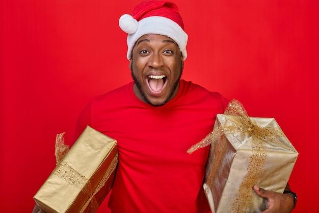 Portret czarnoskórego faceta z uśmiechem zębów w kapeluszu świętego mikołaja trzymającego pod pachami prezenty świąteczne