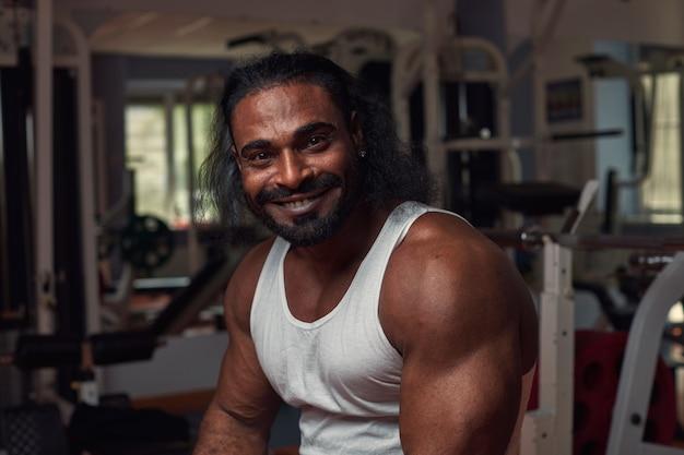 Portret czarnoskórego sportowca, który siedzi na siłowni i uśmiecha się szeroko, sportowa koncepcja stylu życia, wysoka ...