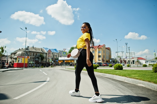 Portret czarny african american kobieta w żółtej koszulce i okularach.
