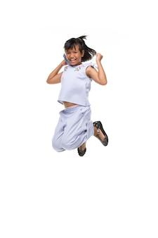 Portret czarny azjatykci dziecka doskakiwanie odizolowywający na bielu.