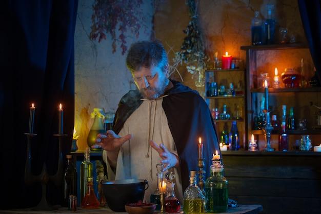 Portret czarodzieja z płonącymi świecami i magicznymi miksturami