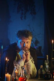 Portret czarodzieja z płonącymi świeczkami i magicznymi miksturami