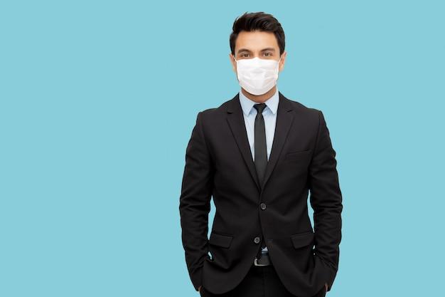 Portret czarującego biznesmena ubranego w garnitur, noszącego ochronną maskę medyczną, aby zapobiec wirusowi covid-19 izolowanemu na jasnoniebieskiej ścianie