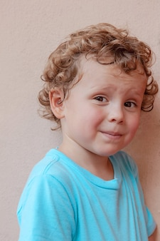 Portret czarującego kręconego blond chłopca w niebieskiej koszulce. dziecko patrzy w kamerę i uśmiecha się przebiegle.