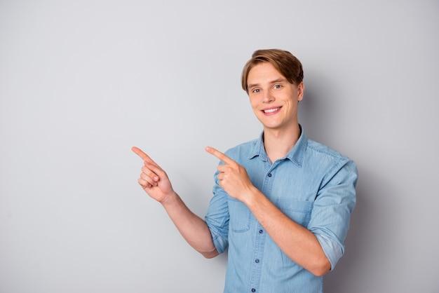 Portret czarującego, pozytywnego faceta fajny promotor wskazujący palec wskazujący copyspace polecam reklamy promocja wybierz rabaty porady nosić dobrze wyglądający strój odizolowany na szarej ścianie