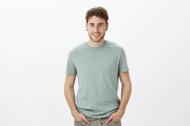Portret czarującego zalotnego, głupkowatego faceta o blond włosach, trzymającego się za ręce na spodniach i uśmiechającego się szeroko, rozmawiającego z przyjaciółmi swobodnie podczas spędzania czasu i relaksu