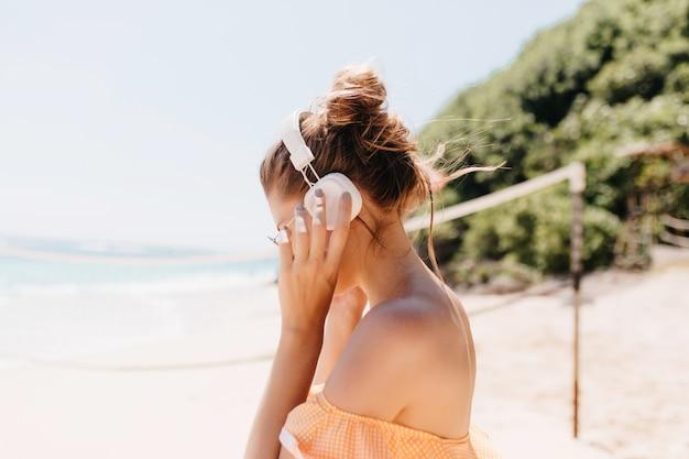 Portret czarującej pani o ciemnych włosach, pozowanie na wybrzeżu oceanu. niesamowita opalona kobieta odpoczywa latem w egzotycznym kurorcie.