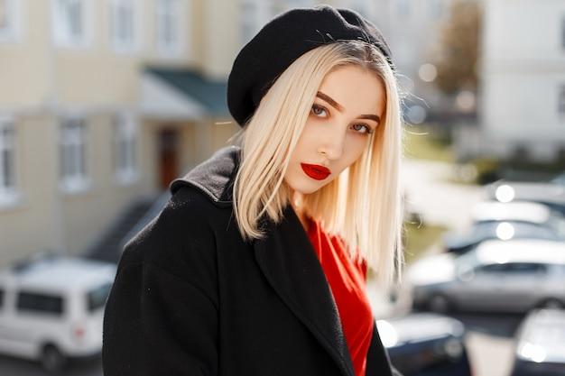 Portret czarującej pięknej blondynki z czerwonymi seksownymi ustami w czarnym płaszczu w eleganckim berecie w stylowej czerwonej koszuli w słoneczny, ciepły dzień