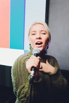 Portret czarujący dziewczyna trzyma mikrofon i śpiewa.