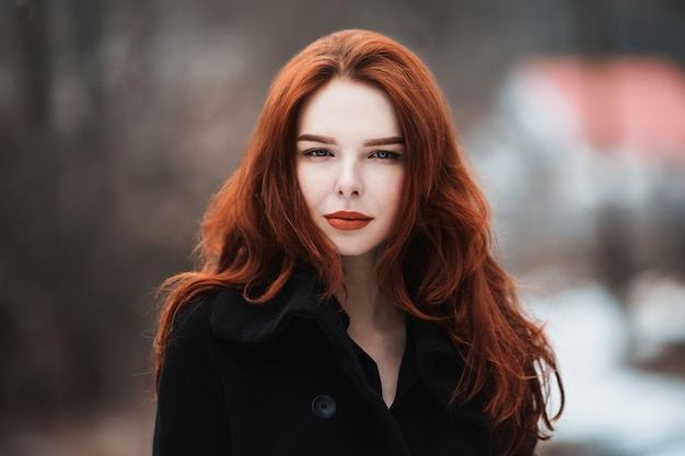 Portret czarujący dziewczynka z długimi rudymi włosami w czarne ubrania. kobieta w czarnym płaszczu pozuje na tle zimy, jesień natura. żeński styl mody ulicznej. piękny elegancki model