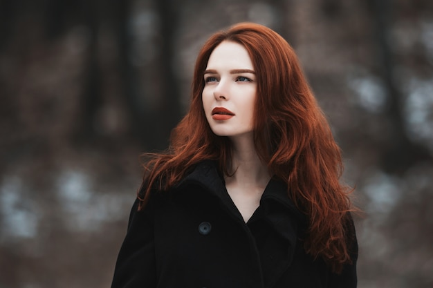 Portret czarujący dziewczynka z długimi rudymi włosami w czarnych ubraniach. kobieta w czarnym płaszczu pozowanie