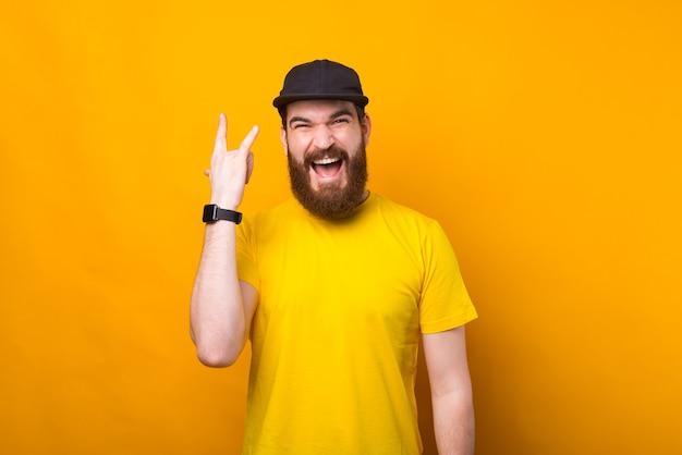 Portret czarujący młody brodaty mężczyzna pokazuje znak rock