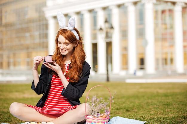Portret czerwona kierownicza kobieta trzyma filiżankę herbata