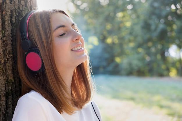 Portret czerwona z włosami nastoletnia dziewczyna słucha muzyka w dużych różowych słuchawkach outdoors opiera opiera drzewo.