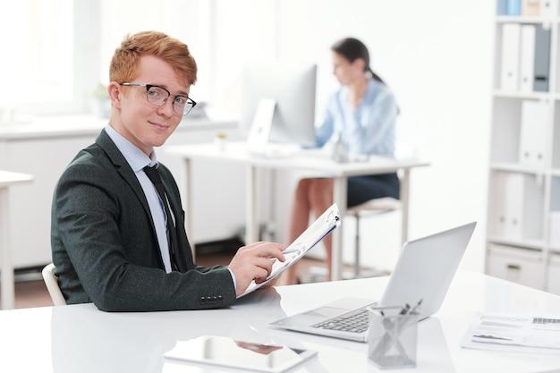 Portret czerwonego na czele młody biznesmen uśmiecha się siedząc przy biurku w biurze, kopia przestrzeń