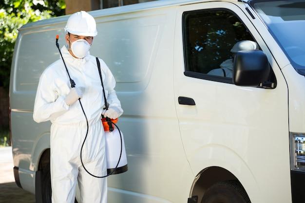 Portret człowieka kontroli szkodników stojący obok samochodu dostawczego
