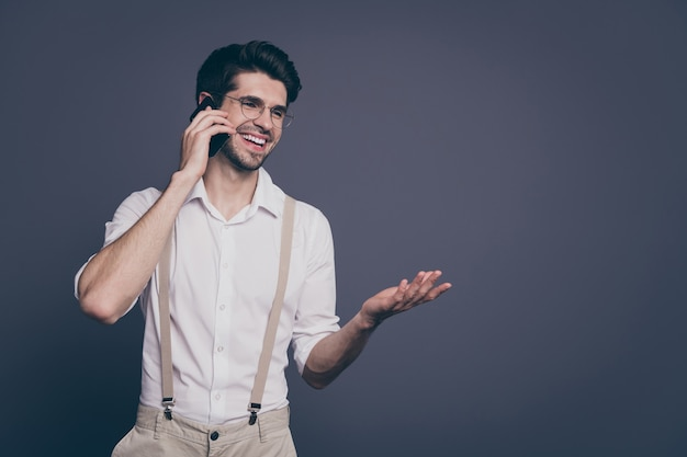 Portret człowieka sukcesu w biznesie rozmawiającego przez telefon z partnerami w przyjaznym nastroju ubrany formalny koszula szelki spodnie specyfikacje.
