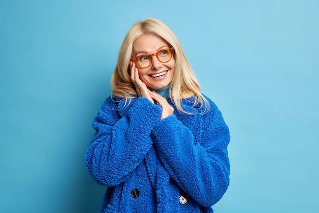 Portret czterdziestoletniej kobiety o blond włosach olśniewający zębaty uśmiech trzyma ręce w pobliżu twarzy wygląda szczęśliwie, ma marzycielski wyraz