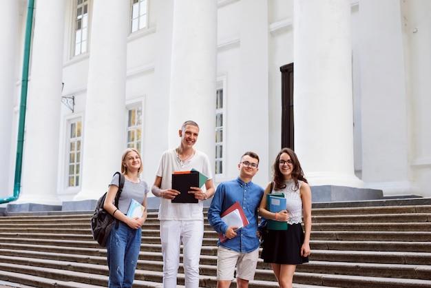 Portret czterech uśmiechniętych studentów przed wykładem w pobliżu budynku uniwersytetu
