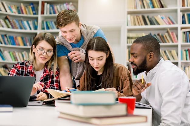 Portret czterech wielorasowych przyjaciół studentów, siedzących przy stole i przygotowujących się do egzaminów lub wykładu. za pomocą różnych książek i laptopa w czytelni w bibliotece kampusu