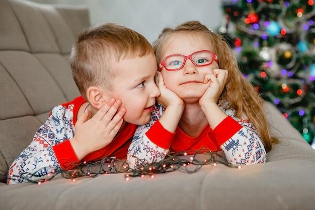 Portret czteroletniego brata bliźniaka i siostry w piżamie w domu na kanapie z choinką