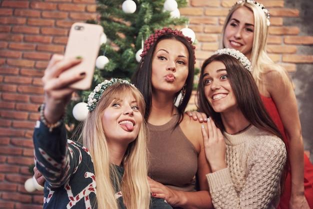 Portret cztery uśmiechniętej dziewczyny z koroną na głowie robi selfie fotografii. nowy rok wesołych świąt