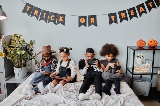 Portret czwórki afrykańskich dzieci korzystających z gadżetów w łóżku pod halloweenową dekoracją...